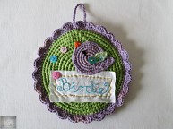 It's a crochet picture with buttons and a lilac birdie.